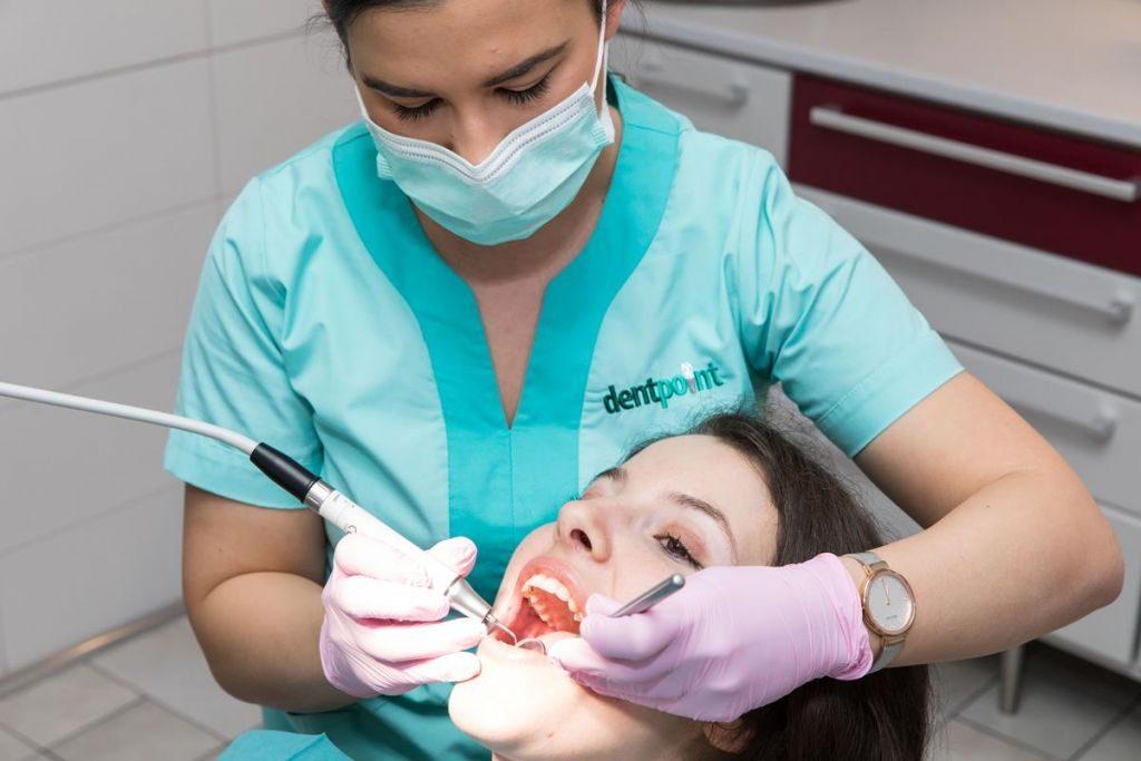 A dentálhigiénikus kezelést ad egy páciensnek.